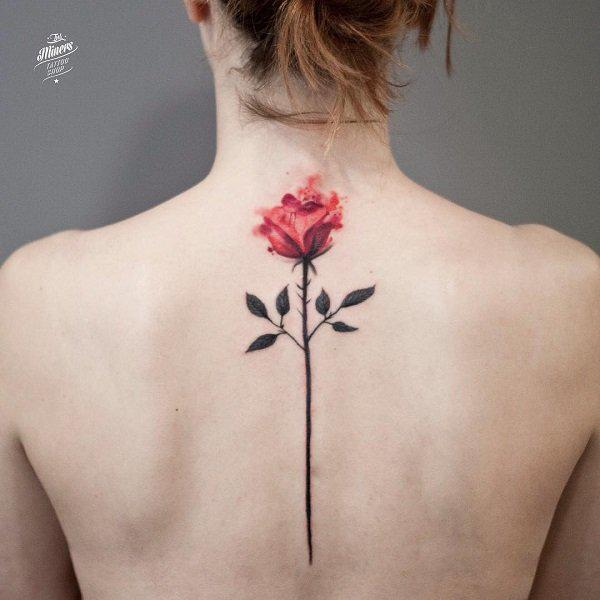 Single stem rose with horns tattoo on spine