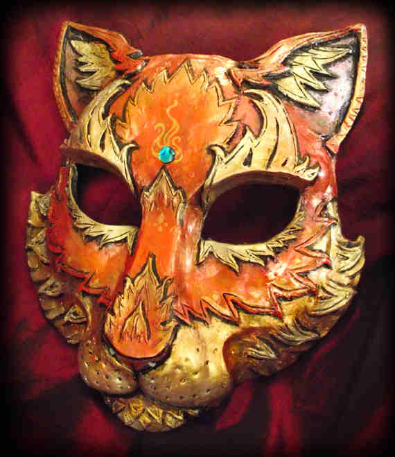 "CAT MASK Molded mask. Handpainted and handsculpted. This has sort of a fire theme going on with a gold sheen to orange. The gem is a piece of the blue abalone. This mask covers most of the face. THe width across the eyes is roughly 6"" and the length from the chin to the forehead is about 7.5""."