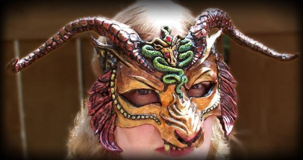 """CHIMERA MASK A mask based on the mythical monster, Chimera, in rich gold, orange and red. Traditionally, the chimera had a lion's body, a lion and goat's heads and a serpent's tail. The artist gave the mask the head of a horned lion with a snake coiling down its snout and goat emblem on its forehead. The goat and snake have gleaming red eyes and a teardrop red gem is set in the snake's forehead. The mask is entirely hand sculpted and painted which has an artist's stamp on the back with the date it was created. The mask is lightweight and the horns are somewhat flexible to reduce the risk of damage. With horns, the mark is 14"""" wide. The main mask is 8"""" wide and 7"""" tall."""