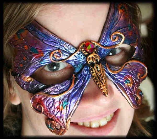 """PURPLE AND GOLD BUTTERFLY MASK This swallowtail butterfly mask is iridescent purple, blue and gold highlights. A red gem with rainbow sheen forms the butterfly's head. This mask is entirely hand sculpted and hand painted with an artist's stamp at the back. Roughly 6"""" wide by 5.5"""" tall."""
