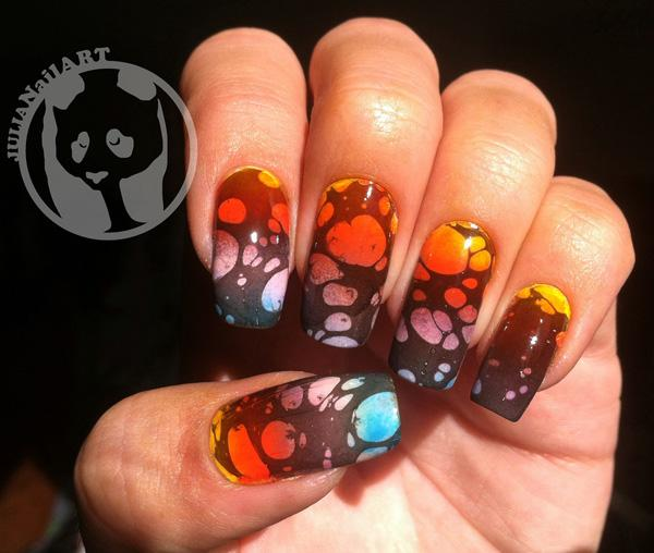 A bubble patterned water marble design using black polish against a gradient background.