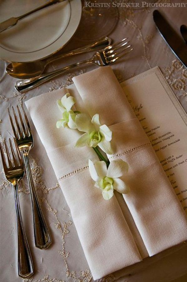 Detail of napkin fold with white orchids