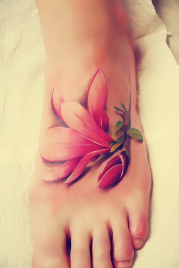 The realistic magnolia tattoo looks like a piece of flower falls on the foot