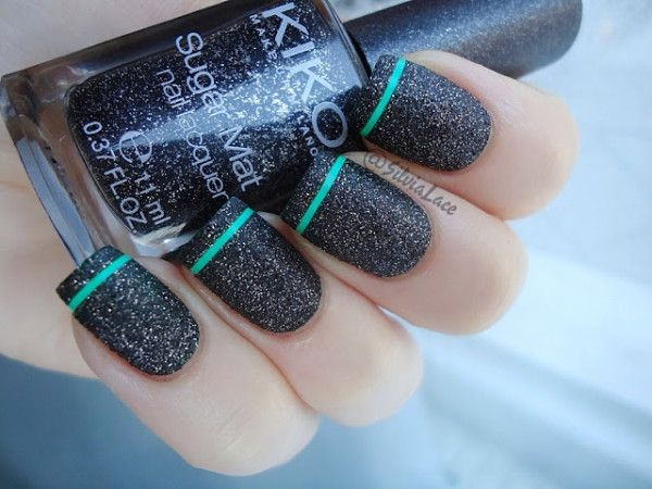 Awesome looking nails in black and silver dust on top lined with a mint green polish at the edge of the nails.
