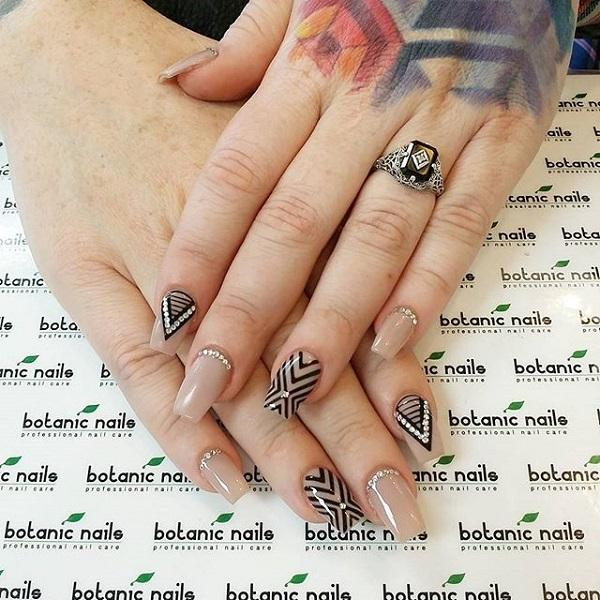 Classic zigzag, horizontal and vertical line nail art design in nude and black polish with silver beads for added effect.