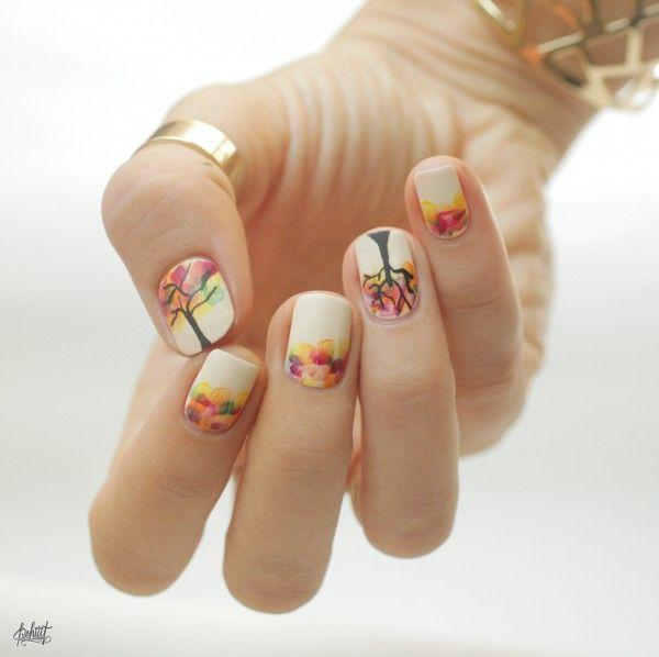 Amazing looking fall tree nail art in multi colored leaves on top of a white background