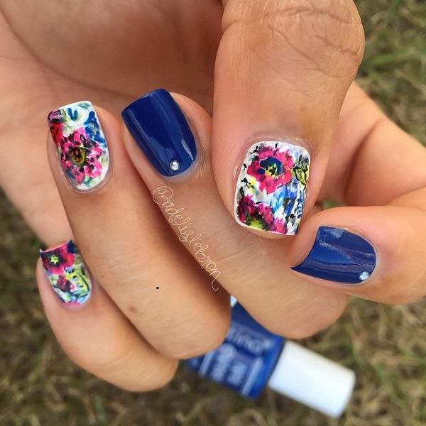 A quirky fall inspired nail art design filled with multi colored flowers in addition to the calm royal blue matte colors topped with silver beads.