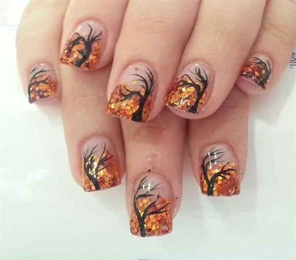 A wonderful looking fall tree nail art design using clear background, black polish for the tree and orange sequins for the leaves.