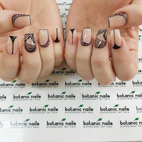 Minimalist tribal themed nail art in clear polish and black details,