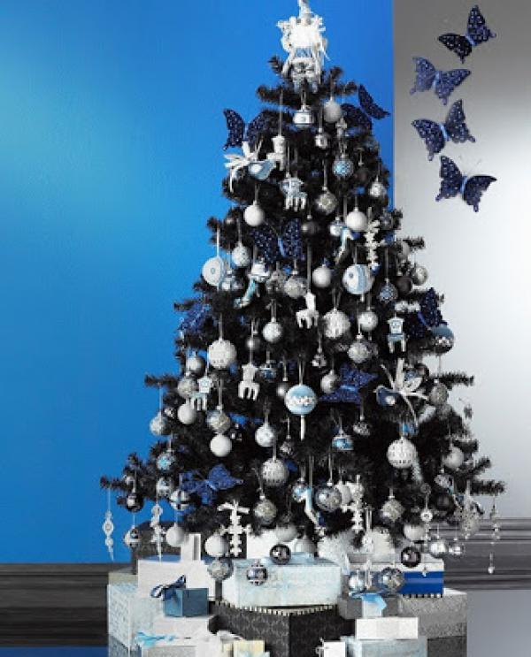 silver blue Christmas tree decorated with non-traditional ornament butterfly