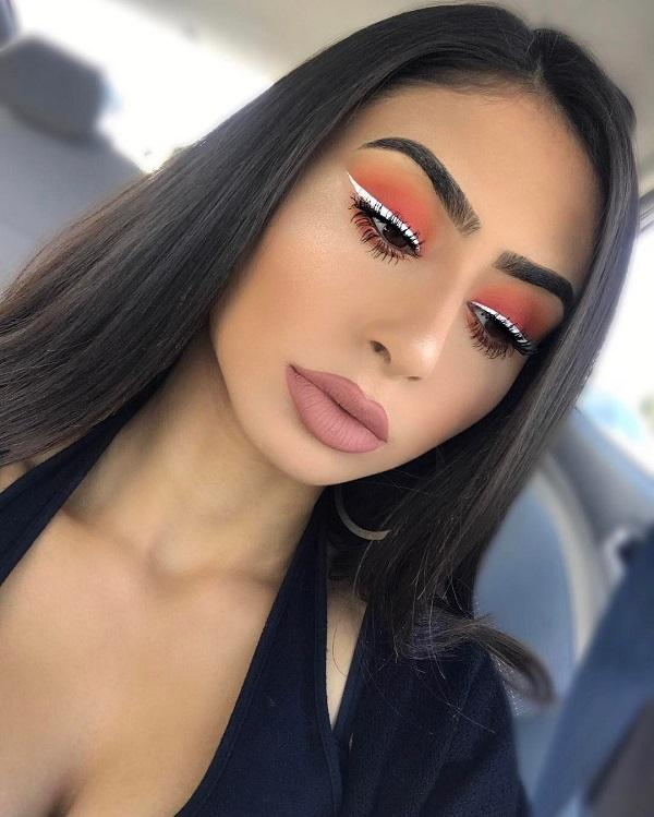 Warm sunset on the eyelids is combined with cold white eyeliner.