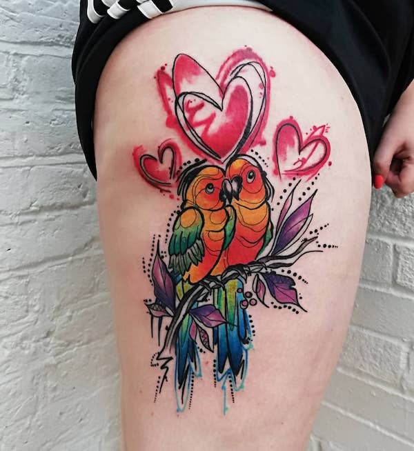 Watercolor lovebird tattoo on thigh